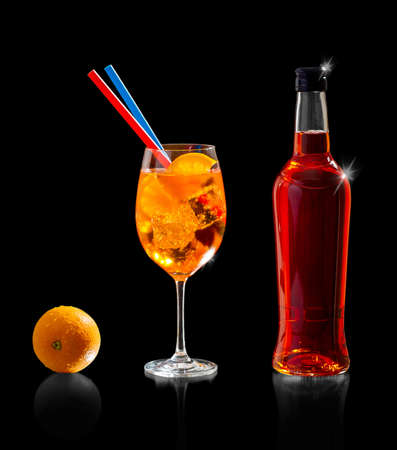 Aperol spritz bottle with orange and straw, isolated on black Stock fotó