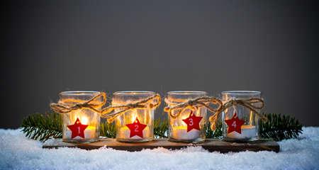 Quatre bougies de l'Avent dans la neige, troisième Avent Banque d'images - 68803747