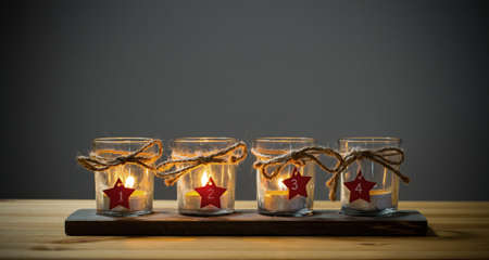 Four Advent candles on wood, third Advent Stock Photo
