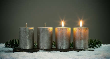 Light four advents candles with matches Stock Photo