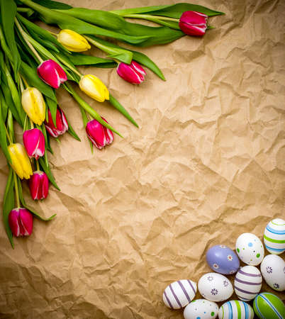 astern: astern egg, tulips on brown crumpled wrapping paper, top view