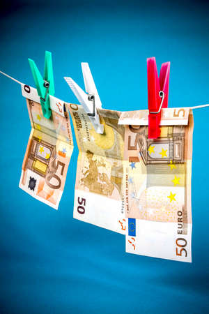 Money laundering from fifty euro notes on blue background