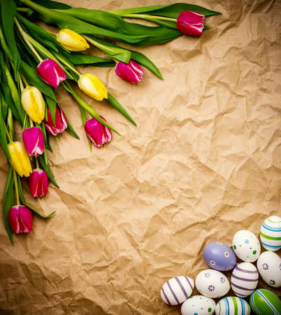 astern egg, tulips on brown crumpled wrapping paper, top view