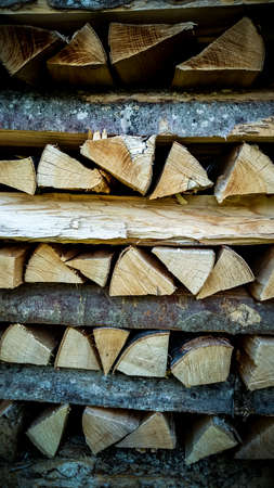 neatly stacked: Neatly stacked firewood as background, soft focus