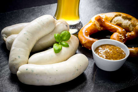 Original Munich sausage with Hefeweizen and pretzel on black slate plate 免版税图像