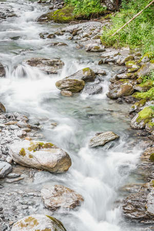 Forest mountain river running over rocks, as small brook 写真素材