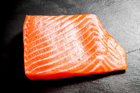 Beautiful salmon fillet on slate plate, top view