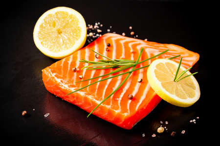 Juicy salmon fillet on black slate plate, top view
