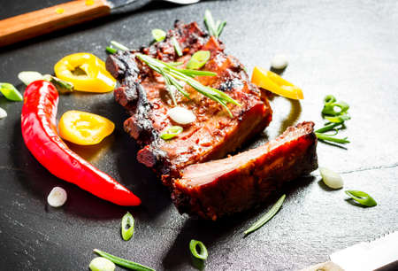 Grilled spareribs on slate plate with cutlery, top view