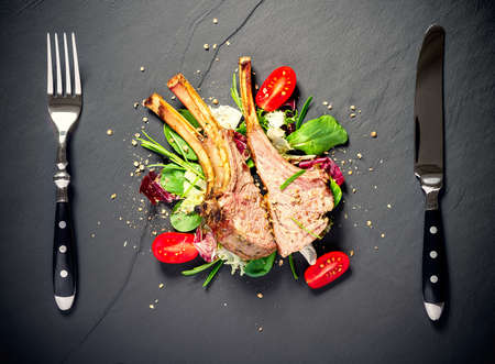 Grilled rack of lamb on slate plate, top view