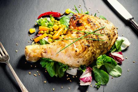 Muslos de pollo a la parrilla en placa de pizarra, vista superior Foto de archivo