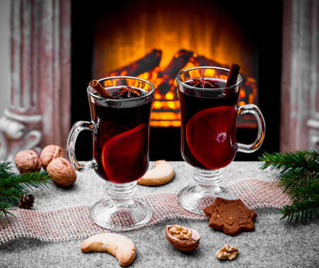 Two mulled wine glasses by the fireplace, christmas time