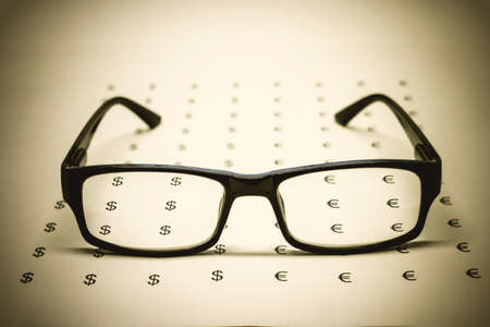 Glasses on paper with dollars and euros, soft focus