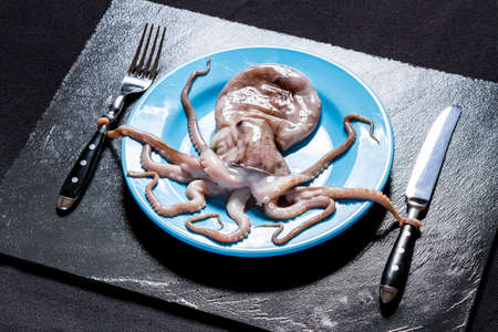 Octopus on blue plate holds cutlery, on black slate