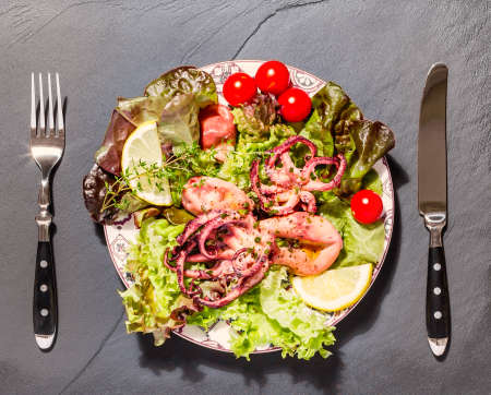 Octopus on blue plate with salad and lemon, on black slate 免版税图像