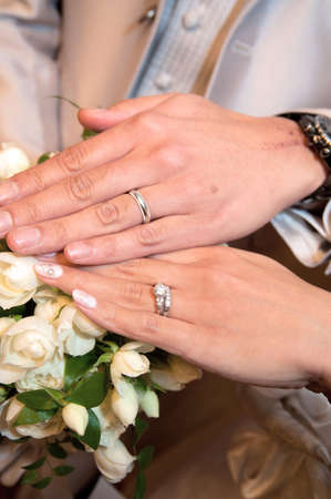 receptions: Wedding ring, two people matching set, up scene superimposed happily hand against the background of the bouquet