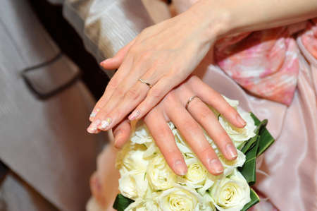 promised: Wedding ring up an overlay of the hands of the bride and groom, you are shining in the background of brilliantly and bouquet