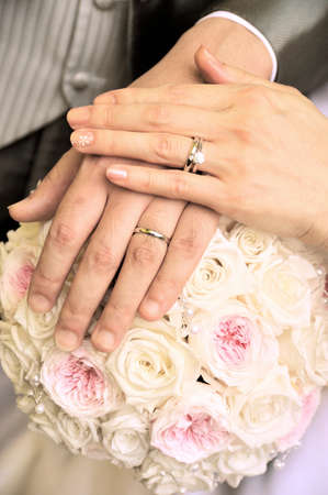 superimposed: Wedding rings superimposed on the bouquet, two people of stylish hand up Stock Photo
