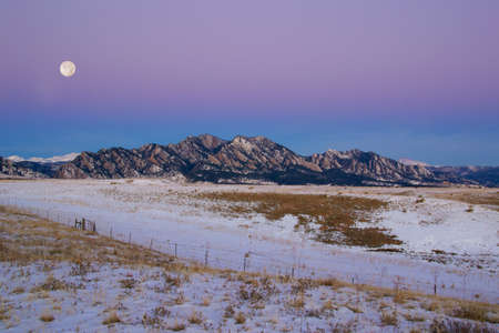 full moon sunrise over Flatirons Mountains
