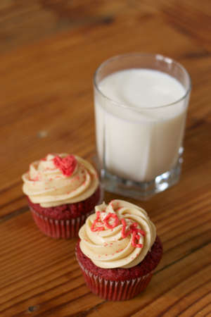Two Red Velvet Cupcakes with a glass of milk Stock Photo