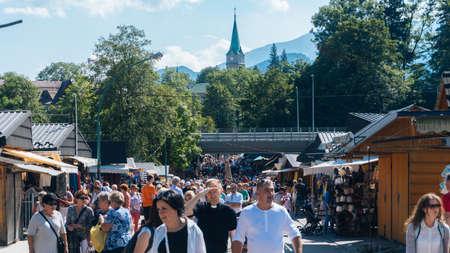 oscypek: ZAKOPANE, POLAND - SEPTEMBER 2, 2016: Market Stalls with Tourists Honey and Pickles in Zakopane. Editorial