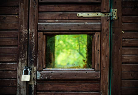 blocking: A wooden frame with lock blocking the view of nature and the window that signifies freedom   Stock Photo