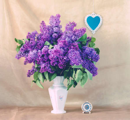Lilac in a Vase, small heart-shaped mirror on the wall and elegant clock. photo