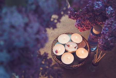Small white candles in a basket, massage oil and essence surrounded by beautiful purple lilac. Stockfoto