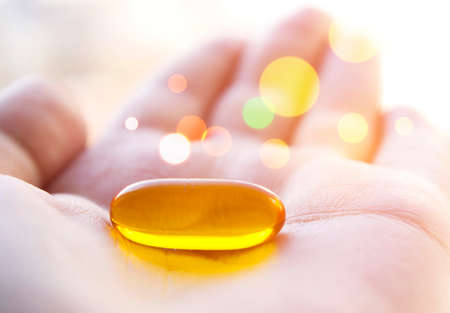 Cod liver oil pill in hand. Magic healing pill. Stock Photo