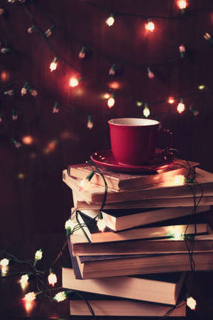 Red cup of tea on a stack of books and Christmas lights in the background. Retro filter