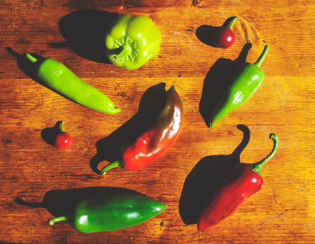 harsh: Red and green peppers on wooden table with harsh light and shadows Stock Photo