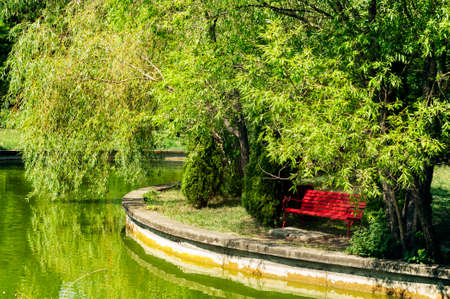Red bench near an emerald green lake and trees.