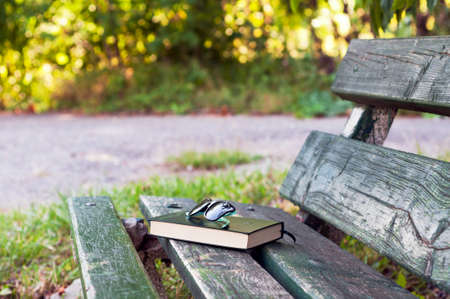 warm things: Sunglasses and book on a bench outdoors in warm light. Enjoying the simple things. Stock Photo