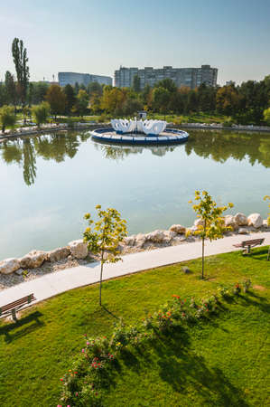 Aerial view of Drumul Taberei Park, also known as Moghioros Park, in Bucharest Romania, in a sunny autumn day. Fountain on the lake and empty alleys