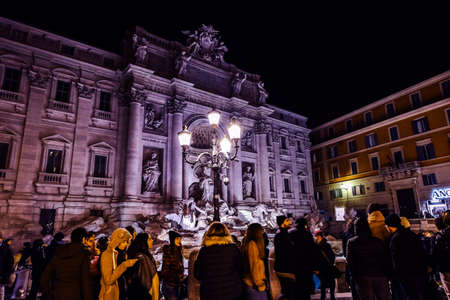Tourists near the Trevi Fountain in Rome at night. Wide view of the location