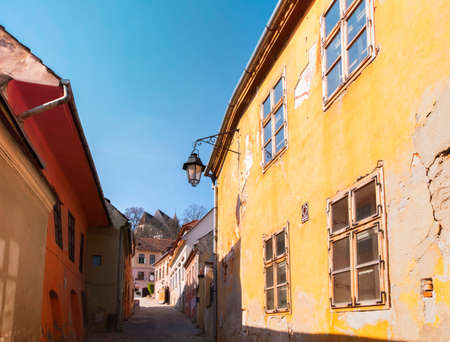 Old colorful houses in Sighisoara citadel on a sunny spring morning. View towards the Church on the Hill