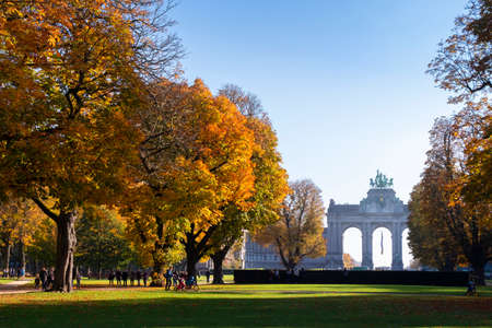Sunny autumn morning in Cinquantenaire park with the Triumphal Arch in view and people strolling on alleys Redactioneel