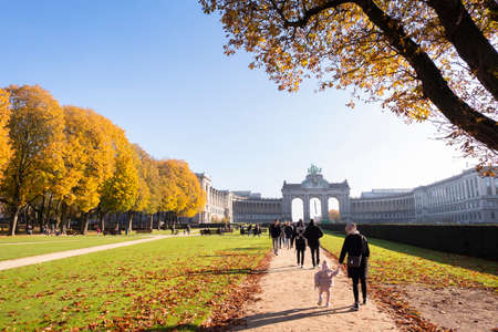 People strolling on alleys on a sunny autumn morning in Cinquantenaire park.