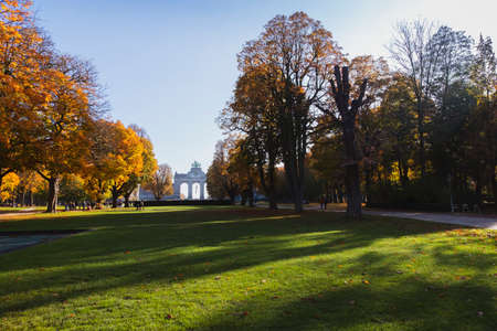 Autumn morning in Cinquantenaire park with the Triumphal Arch in view and people strolling on alleys Redactioneel