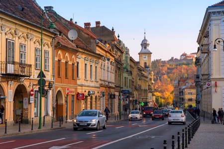 raffic on Muresenilor Street, in the historic center of Brasov city on an autumn day, in sunrise light.