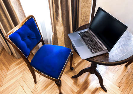 Elegant lightweight laptop with blank screen on a wooden table. Top view