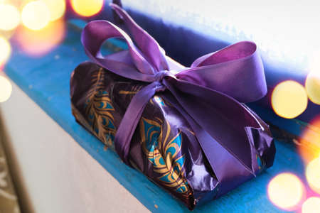 Purple and gold wrapped gift for Christmas on blue wooden board. Beautiful bright light. Unperfect wrapping, hand-made