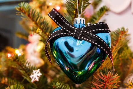 Blue heart-shaped bauble on the branch of the Christmas tree.