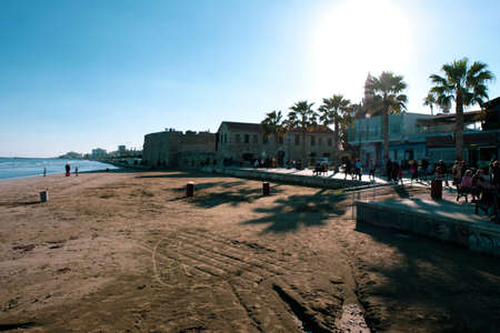 People strolling along Finikoudes beach in Larnaca on a sunny day in January.