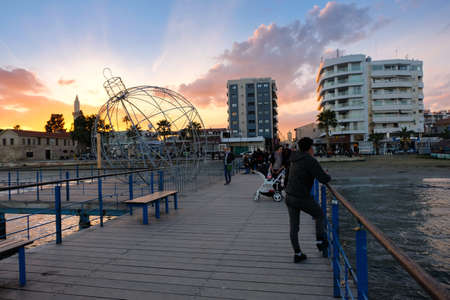 People on the pier at sunset in Larnaca during the holiday season Redactioneel