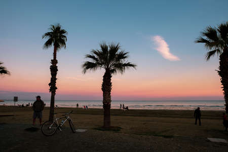 People at Finikoudes Beach, taking a stroll at sunset. Palm tree silhouettes and colorful sky in view.