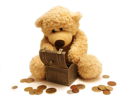 euromoney:  Teddy-bear sitting near a trunk and eurocentes lie around isolated in white.                                                              Stock Photo
