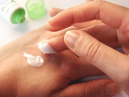 piel humana: femenino manos applaing una crema de cerca.
