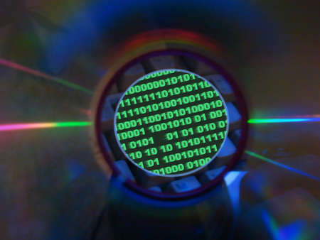 keyboard & binary code visible through compact disk hole