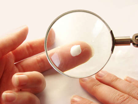 female hand holding a creams drop testing it under a magnifier.
